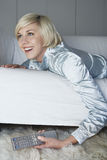 Kvinna på Sofa With Remote Control Arkivbild