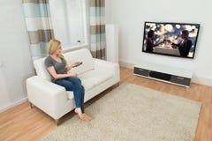 Kvinna på Sofa Watching Movie Royaltyfri Bild