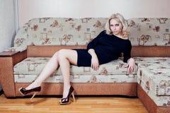 Kvinna på soffan arkivbild