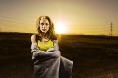 Kvinna på solnedgången med filten Arkivfoton