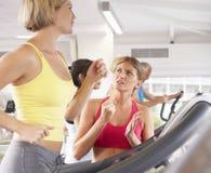 Kvinna på springmaskinen i idrottshall som uppmuntras av den personliga instruktören Royaltyfri Bild