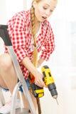 Kvinna på stege genom att använda drillborren royaltyfri fotografi
