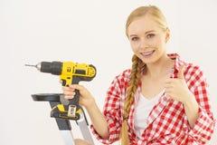 Kvinna på stege genom att använda drillborren arkivfoto
