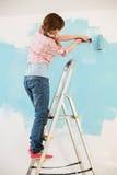 Kvinna på stegemålningväggen med målarfärgrullen Royaltyfri Bild
