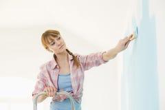 Kvinna på stegemålningväggen med målarpenseln Royaltyfri Foto