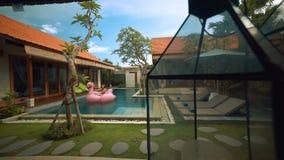 Kvinna på stor uppblåsbar flamingo i villapöl stock video