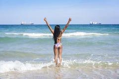 Kvinna på stranden, händer upp fotografering för bildbyråer