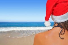 Kvinna på stranden i den santas hatten Royaltyfri Foto