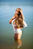 Kvinna på stranden i en kort vit klänning Royaltyfri Fotografi