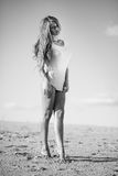 Kvinna på stranden i en kort vit klänning Royaltyfri Bild