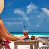 Kvinna på stranden med chaise-vardagsrum royaltyfria bilder