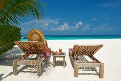 Kvinna på stranden med chaise-vardagsrum arkivfoto