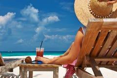 Kvinna på stranden med chaise-vardagsrum royaltyfri fotografi