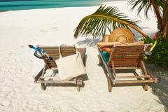 Kvinna på stranden med chaise-vardagsrum royaltyfria foton