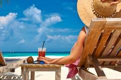 Kvinna på stranden med chaise-vardagsrum arkivfoton