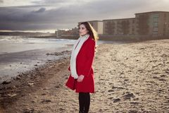 Kvinna på stranden med ett rött lag fotografering för bildbyråer