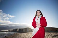 Kvinna på stranden med ett rött lag arkivfoto