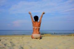Kvinna på stranden som sitter och lyfter henne armar Royaltyfri Foto
