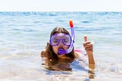 Kvinna på strandsemesterferier med snorkeln som ligger i havet med att snorkla att le för maskering som är lyckligt tycka om sole fotografering för bildbyråer
