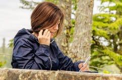 Kvinna på telefonen i en parkera Arkivfoto
