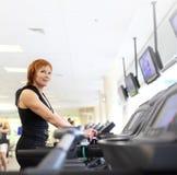 Kvinna på trademill i idrottshall Royaltyfria Foton