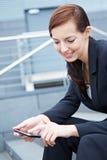 Kvinna på trappa genom att använda smartphone royaltyfria bilder