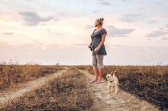 Kvinna på vägen med en liten hund Royaltyfria Bilder