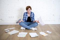 Kvinna på vardagsrumgolvet med räknemaskinen och banken och räkningar skrivbordsarbete och dokument som gör inhemsk finansiell re Arkivfoto