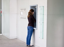 Kvinna på atm-maskinen Arkivfoto
