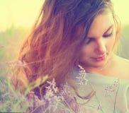 Kvinna på en äng med Violet Flowers Royaltyfri Foto