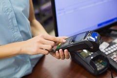 Kvinna på kassaapparaten som betalar med kreditkorten Arkivbild