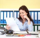 Kvinna på kontoret som läser ett brev Fotografering för Bildbyråer