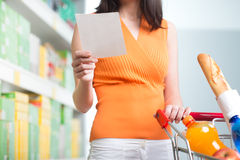 Kvinna på supermarket med shoppinglistan Royaltyfria Bilder