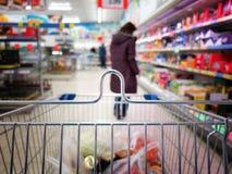 Kvinna på supermarketen med trolleyen Royaltyfri Foto