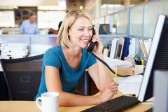 Kvinna på telefonen i upptaget modernt kontor Arkivfoton