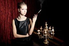 Kvinna rök med cigaretthållaren, retro stil Fotografering för Bildbyråer