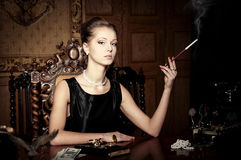Kvinna rök med cigaretthållaren, retro stil Arkivfoton