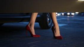Kvinna` s lägger benen på ryggen i häl som kliver ut ur bilen på natten