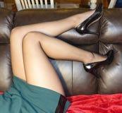 Kvinna` s lägger benen på ryggen i ren strumpbyxor och höga häl Royaltyfri Foto