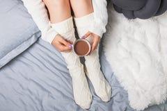 Kvinna` s lägger benen på ryggen i sockor och räcker hållande kakao eller kaffe Royaltyfri Bild
