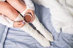 Kvinna` s lägger benen på ryggen i sockor och räcker hållande kakao eller kaffe Arkivfoton