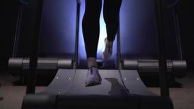 Kvinna s lägger benen på ryggen i vita gymnastikskor och damasker som kör på trampkvarnen i idrottshall stock video