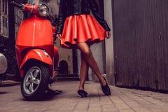 Kvinna` s lägger benen på ryggen nära den röda motoriska sparkcykeln royaltyfri fotografi