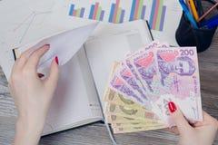 Kvinna` s räcker att sätta ukrainska pengar in i ett kuvert royaltyfri fotografi