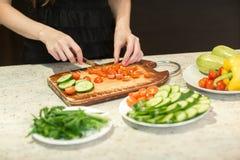 Kvinna` s räcker bitande grönsaker royaltyfri foto