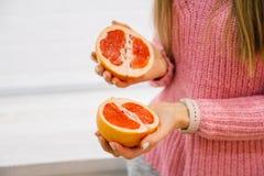Kvinna` s räcker den bitande nya grapefrukten på kök Bitande apelsin för flicka med kniven sund livsstil för begrepp arkivfoto
