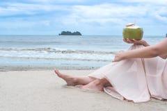 Kvinna` s räcker den hållande kokosnöten på den tropiska stranden Arkivbild