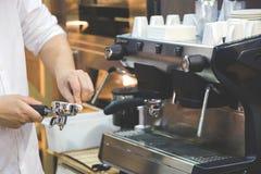 Kvinna` s räcker den rena hållaren för kaffemaskin arkivbild