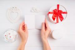 Kvinna` s räcker det hållande tomma hälsningkortet på vit bakgrund med romantisk garnering som giftbox, ram i form av hjärta, äng royaltyfri foto