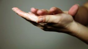 kvinna` s räcker fördelning av en kräm- ower fingrarna